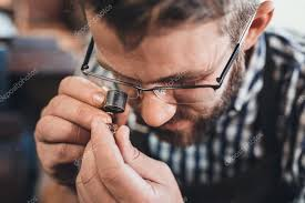 jeweller examing a piece of jewellery through a loupe